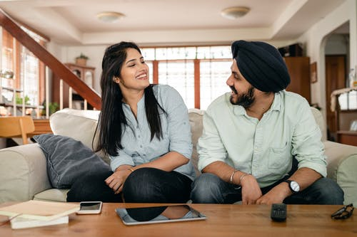 Cheerful young Indian man and woman in casual clothes smiling and looking at each other while sitting on sofa at home