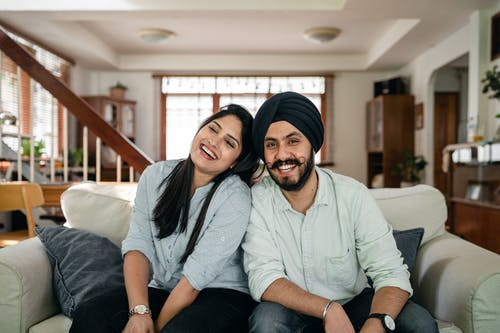 Delighted young Indian couple relaxing and laughing together on couch at home