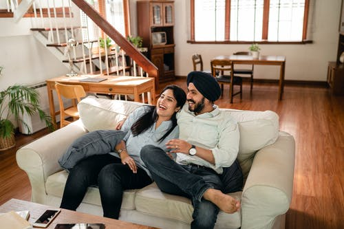 Laughing young Indian couple cuddling on sofa