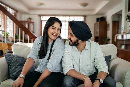 Loving young Indian couple flirting and smiling at home