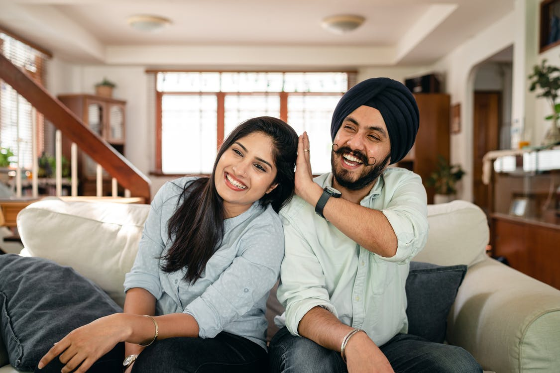 Playful Indian spouses having fun on sofa during weekend