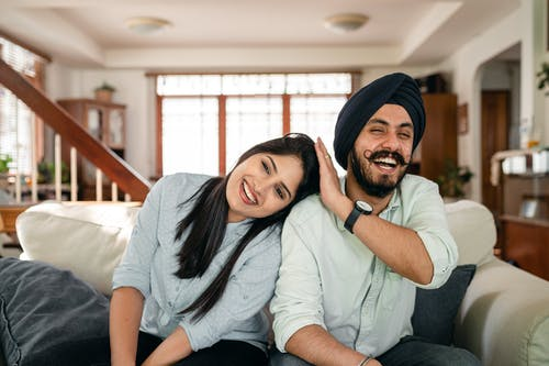 Young happy casual Indian woman leaning on shoulder of boyfriend in traditional turban while having fun together in cozy living room