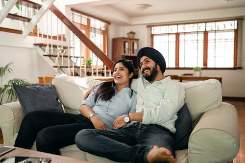 Joyful young Indian couple cuddling while watching funny film on TV