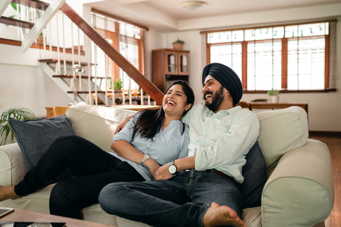 Laughing young Indian couple watching comedy movie together at home