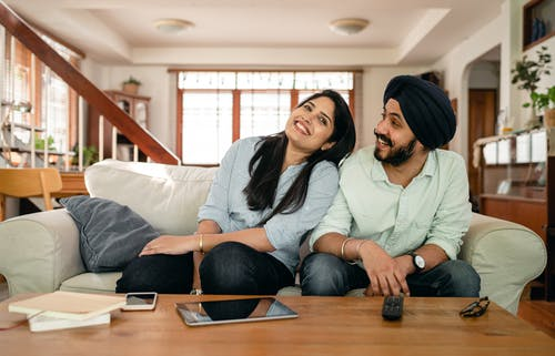 Optimistic young Indian lady in casual wear flirting with happy boyfriend while chilling on comfortable couch