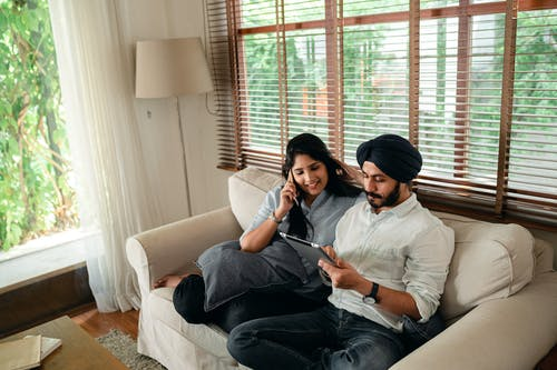 Young Indian man browsing tablet while woman talking on smartphone on couch