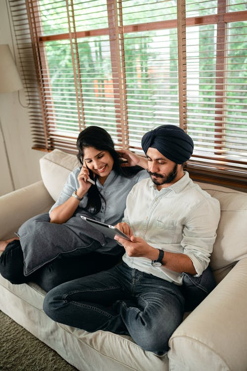 Happy ethnic couple using smartphone and tablet at home