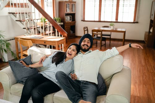 Delighted ethnic couple having fun on sofa in cozy apartment