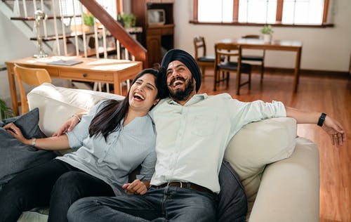 Smiling Indian couple cuddling in living room