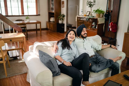 Delighted Indian couple hugging on sofa in cozy apartment