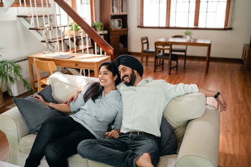 From above of optimistic ethnic man and woman in casual outfit embracing and resting together on cozy sofa while enjoying romantic holiday at home
