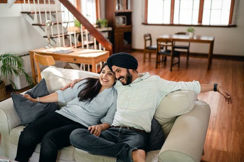 Cheerful ethnic couple cuddling on sofa at home