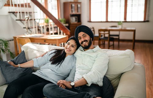 Happy ethnic couple embracing on sofa at home