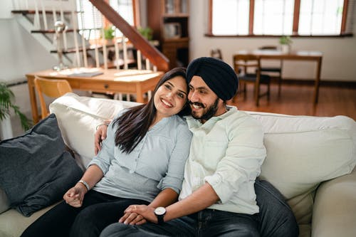 Positive ethnic couple resting on cozy couch in living room