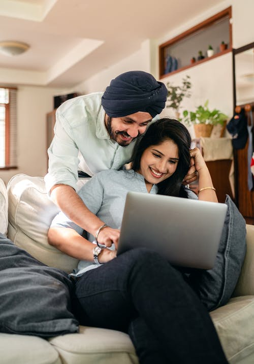 Smiling ethnic man bending over positive ethnic wife using laptop at sofa and pointing at keyboard while resting at home