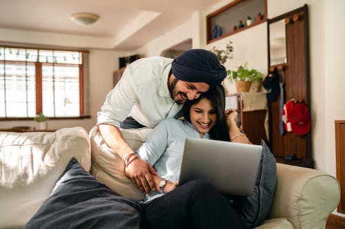 Cheerful man bending over sofa and putting hand on hand of ethnic wife sitting with laptop while looking at screen together in living room