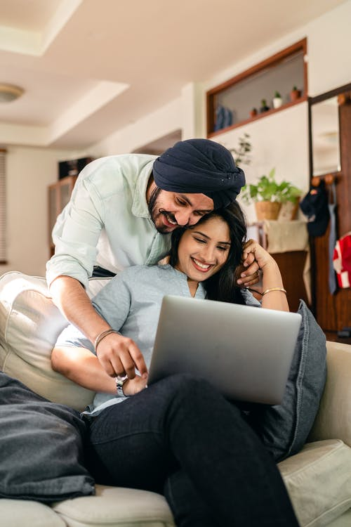 Positive ethnic man bending over ethnic wife using laptop on sofa and pointing on screen while resting at home together