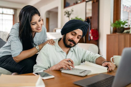 Ethnic woman looking at ethnic husband working with calculator