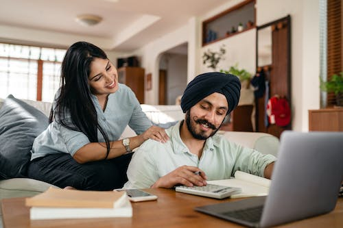 Positive ethnic man sitting at coffee table with laptop and smartphone and books and notebook and calculating while smiling ethnic wife sitting on sofa and supporting and watching behind