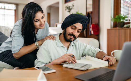 Focused ethnic man calculating while wife watching behind