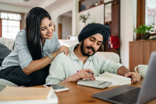 Happy young Indian woman supporting husband during freelance work at home