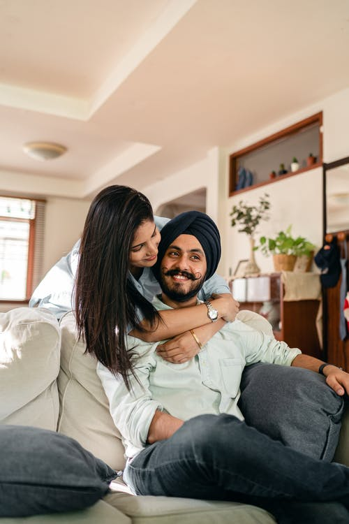 Happy young Indian woman hugging husband sitting on sofa at home