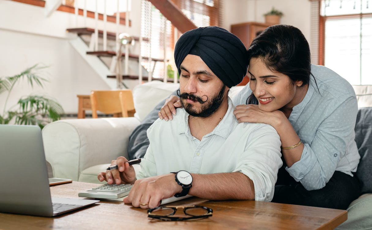 Cheerful ethnic couple using calculator while sitting at table