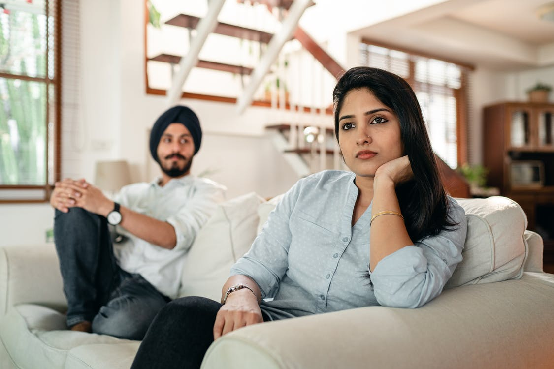 Offended young Indian female sitting on couch with husband
