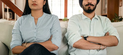 Crop thoughtful young man and woman in casual clothes sitting on sofa with crossed arms after having argue