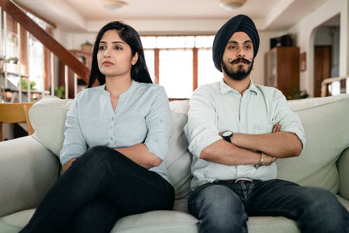 Resentful young Indian couple ignoring each other while sitting on couch together with crossed arms