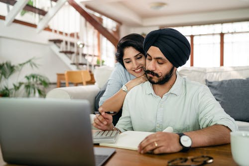 Cheerful young Indian woman cuddling and supporting serious husband working at home with laptop and counting on calculator