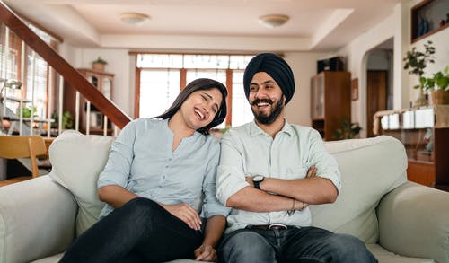 Optimistic young Indian man and woman in casual outfits laughing and having fun while resting together on comfortable sofa during weekend