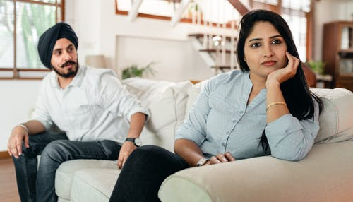 Serious couple in conflict sitting on couch in living room