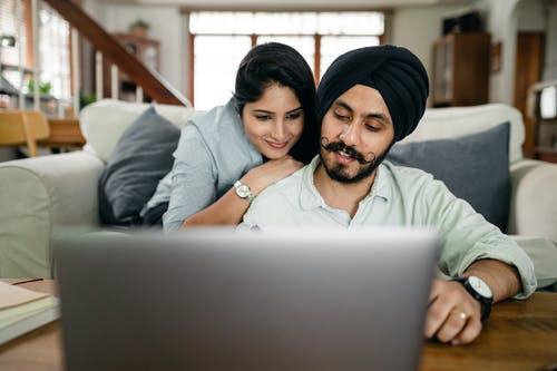 Cheerful ethnic couple using laptop and smiling