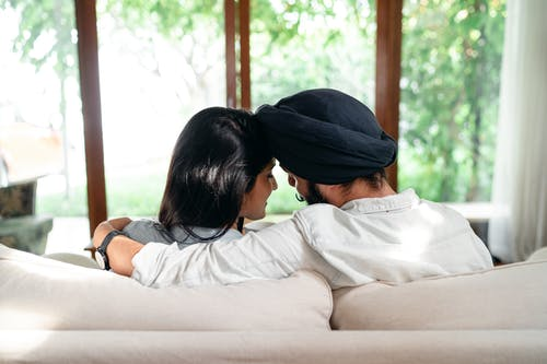 Cuddling young Indian couple resting on sofa