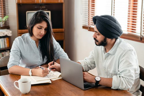 Indian man and woman sitting at table and working on notebook with bills and laptop while discussing business at home