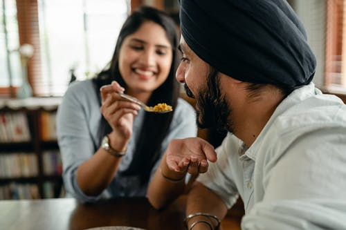 Positive girlfriend feeding crop Indian boyfriend with delicious food