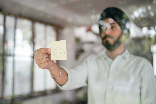 Indian guy in turban and shirt with curled mustache sticking paper with INDIA STAY HOME inscription while standing behind glass wall during COVID 19 pandemic