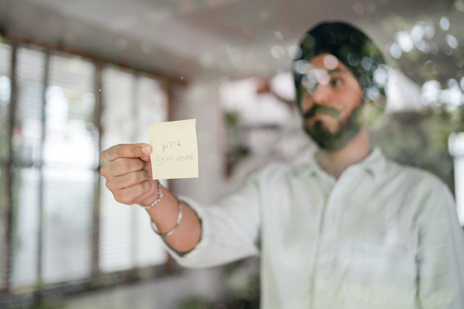 Indian man showing note with inscription on paper through glass