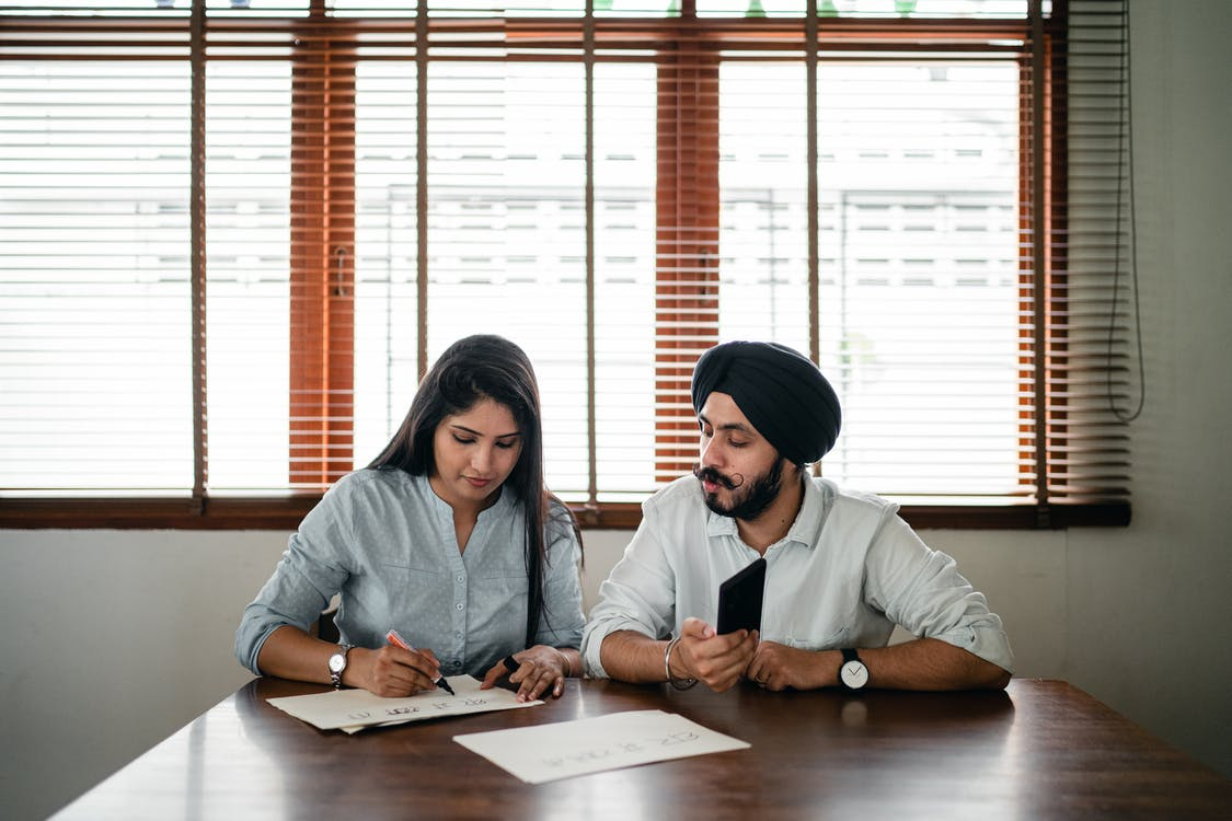 Indian woman and man writing posters at table in light office