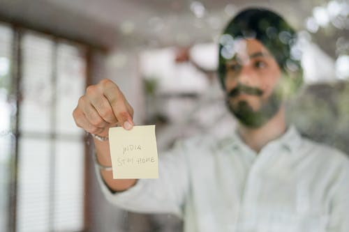 Indian man showing paper sheet while standing behind glass wall