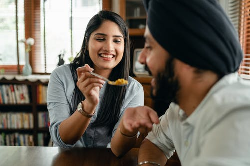 Positive young ethnic lady feeding boyfriend with delicious food