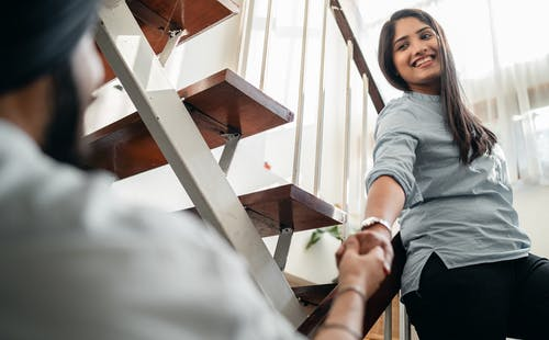 Happy young ethnic couple holding hands on staircase at home