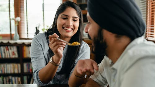 Happy young Indian woman smiling and feeding positive hungry boyfriend with delicious saffron rice
