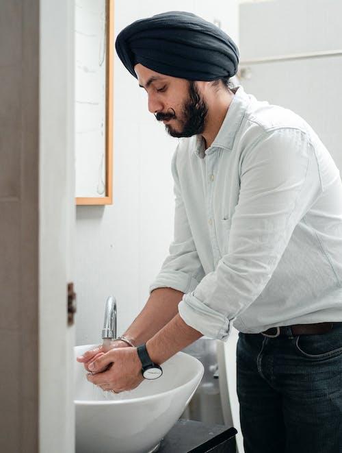 Man in White Dress Shirt Washing his Hands