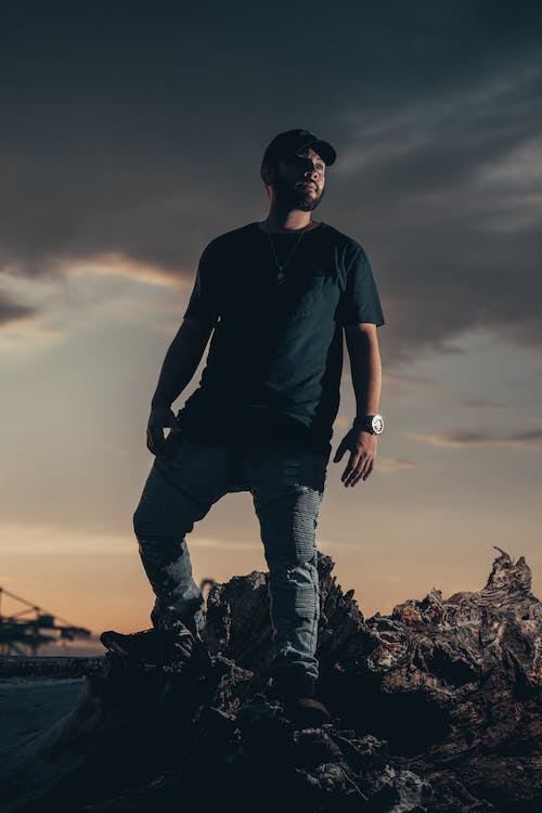 Man in Black Crew Neck T-shirt and Blue Denim Jeans Standing on Brown Rock during