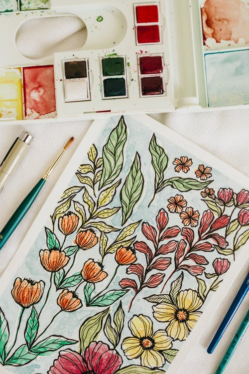 Top view of paper sheet with colorful flower painting placed on table near box with watercolor