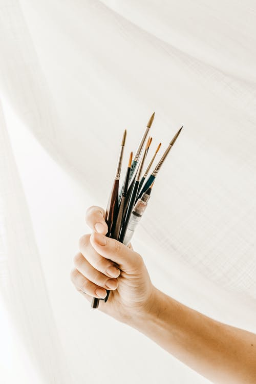 Unrecognizable artist showing set of paintbrushes against white drapery during work in studio