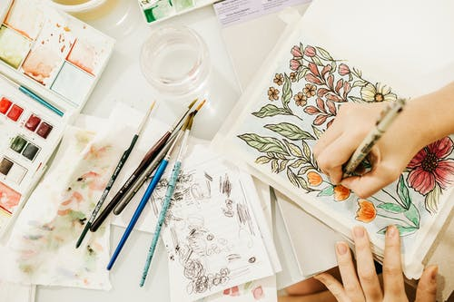 Crop artist painting flowers in sketchbook