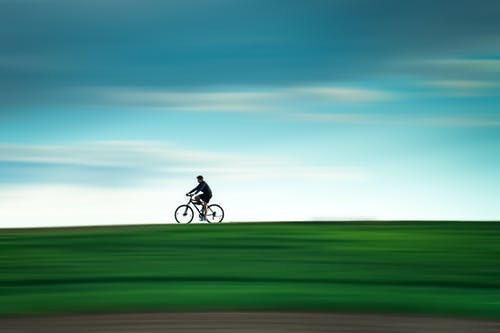 Side view of anonymous sportsman riding bicycle in green valley under bright sky